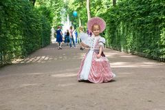 Little girl in 1800`s dress with fan. SAINT PETERSBURG, RUSSIA - AUGUST 18, 2017: Little girl in 1800`s dress with fan for a walk in Summer Park. This park is Royalty Free Stock Photos