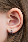 The little girl's ear. With an earring, inserted into the ear Royalty Free Stock Photography
