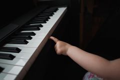Little girl`s hand next to the piano. A small finger tries to press the keys. No face. Close up. Little girl`s hand next to the piano. A small finger tries to Stock Photography