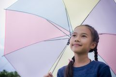 Little girl`s hold umbrella smile and looking at on the rainy season Royalty Free Stock Photography