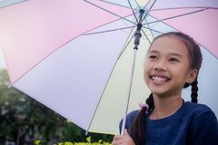 Little girl`s hold umbrella smile and looking at on the rainy season stock image