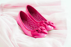 Little girl's pink ballerina shoes on tutu skirt Royalty Free Stock Image