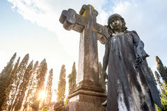 The little girl`s statue premature dead, near the stone cross Royalty Free Stock Image