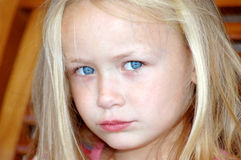 Little girl sad. A beautiful little caucasian white girl child head portrait with bright blue eyes, long blond hair and sad expression in her pretty face Stock Images