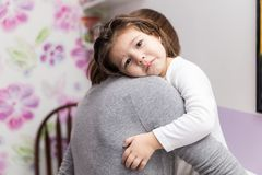 Mother Comforting Toddler At Home. Little girl with sad expression embracing mother at home royalty free stock image