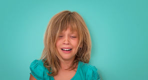 Little girl with sad expression and tears. Crying child on turquoise background. Emotions.