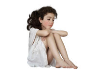Little girl with sad eyes. His head resting on his hands, in the white lacy nightgown on white background Royalty Free Stock Images
