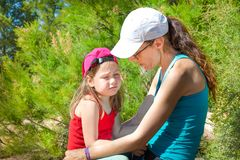 Little girl with sad face expression sitting on the legs of a woman in the forest stock photography