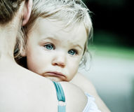 Little girl with sad look on mother's shoulder Stock Photos