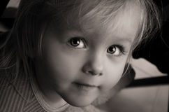 Little girl sad serious eyes. Closeup. Stock Photos