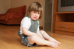 Little girl sad. Little girl sitting on the floor and crying Royalty Free Stock Images