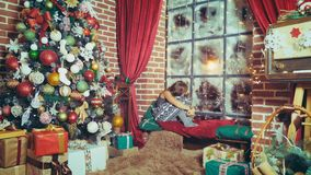 The girl is waiting for the holiday. Little girl is sad sitting by the window on Christmas Eve. New Year. Christmas. Waiting for Santa. The girl is looking out stock footage