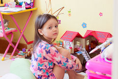 A little girl is sad among the toys stock photo