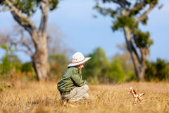 Little girl on safari. Adorable little girl in South Africa safari running in a bush with giraffe toy Royalty Free Stock Photography