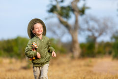 Little girl on safari. Adorable little girl in South Africa safari running in a bush with giraffe toy Stock Images