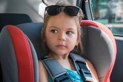 Little girl in a safety car seat. Safety and security. Safe driving. Child transportation safety. royalty free stock images