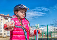 Little girl in a safety helmet riding a bicycle Stock Photo