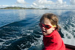 Little girl sailing. On a yacht at sea stock photography