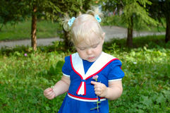 Little girl in sailor blue dress walk in the park. Royalty Free Stock Photo