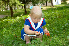 Little girl in sailor blue dress walk in the park. Royalty Free Stock Images
