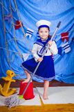 A little girl in sailor clothes. Sea theme royalty free stock photo