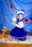 A little girl in sailor clothes. Sea theme. Young girl playing with nautical things. Summer sea dream and imagination. Travel and adventure concept stock photography