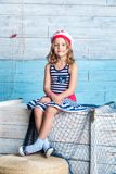Little girl sailor sitting on box Royalty Free Stock Image