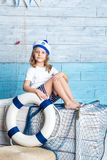 Little girl sailor sitting on box Stock Images