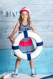 Little girl sailor standing and keeps lifebuoy Royalty Free Stock Photo