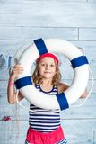 Little girl sailor standing and keeps lifebuoy Stock Photo
