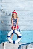 Little girl sailor standing and keeps lifebuoy. Looking at camera Royalty Free Stock Images