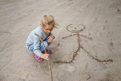 Little girl sand draws funny man Stock Image