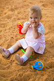 Little girl in sandbox. The little girl is sitting in sandbox Stock Photography