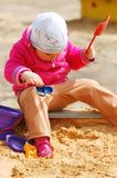 The little girl in a sandbox Stock Images