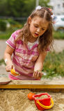 Little girl in sandbox. Little girl playing in the sandbox Royalty Free Stock Image