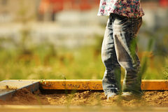 Little girl in a sandbox. Little girl playing in a sandbox Royalty Free Stock Photos