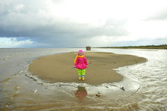Little girl on a sandy autumn beach Stock Photo