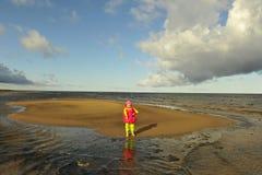 Little girl on a sandy autumn beach Royalty Free Stock Image