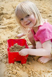 Little girl on sandy beach with bucket and spade Royalty Free Stock Photography