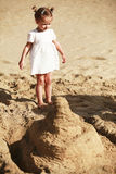 Little girl on sandy beach Stock Image