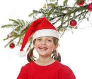 Little girl with santa cap and christmas tree Royalty Free Stock Photography