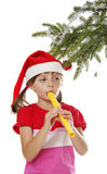 Little girl with santa cap playin the flute Royalty Free Stock Photos