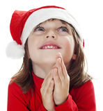 A little girl with a santa cap praying Royalty Free Stock Image