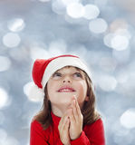 A little girl with a santa cap snowy bokeh Royalty Free Stock Image