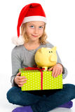 Little girl with Santa- Claus cap and piggy bank Royalty Free Stock Image
