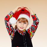 Little girl in santa claus hat ale a lesson. Happiness, winter holidays, new year, and childhood Stock Photos