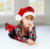 Little girl in santa claus hat ale a lesson. Royalty Free Stock Photos