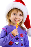 Little girl in santa claus hat with candy Royalty Free Stock Images