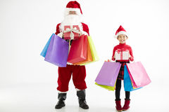 little girl and santa claus holding shopping bags Royalty Free Stock Photography