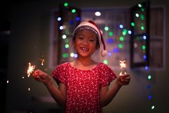 Little girl in Santa Clause hat enjoy celebrate Christmas Eve. Little girl with Santa Clause hat enjoy celebrate Christmas Eve or New year party with sparkler on royalty free stock photography